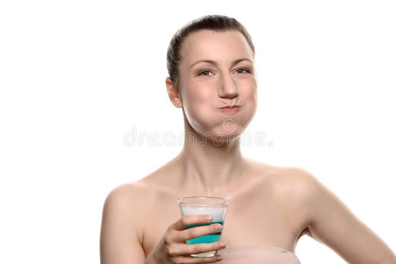 使用漱口的妇女在口腔卫生惯例期间 免版税库存图片