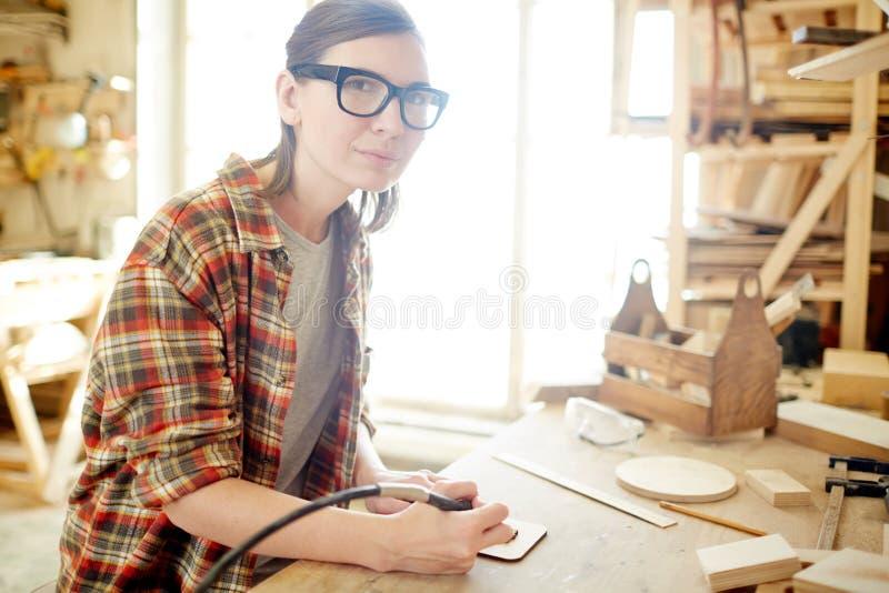 使用烙画燃烧器的女性木匠 免版税库存图片