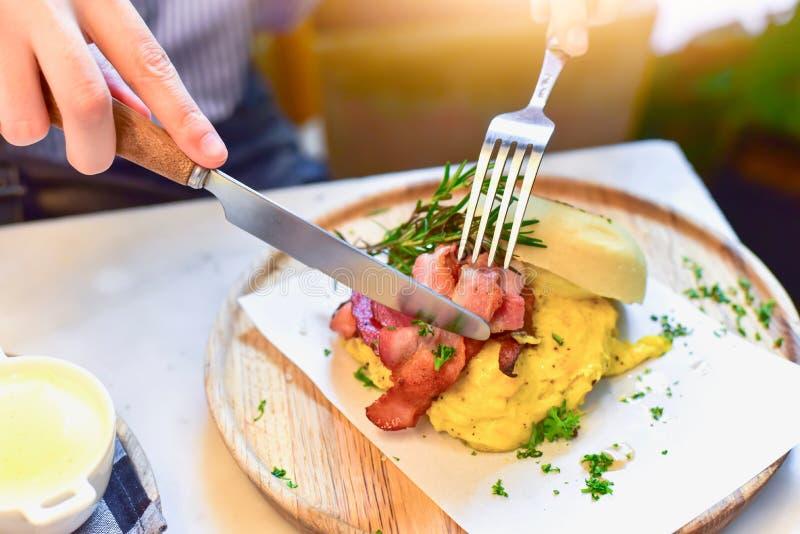 使用烟肉和鸡蛋的刀子和的叉子的手切英格兰式松饼 免版税库存照片