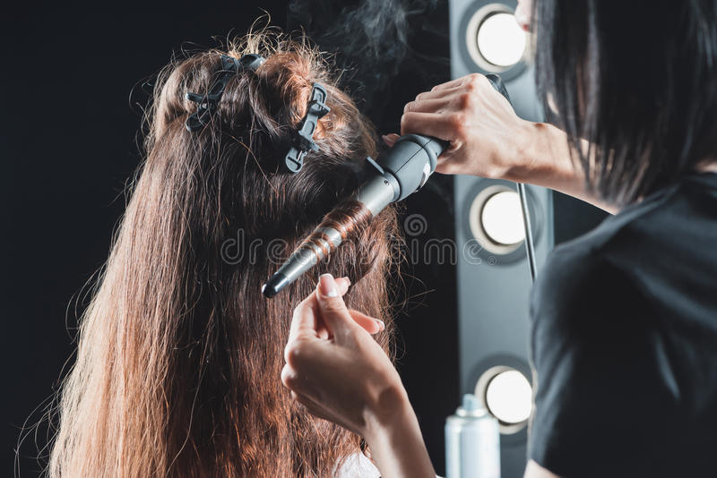 使用烫发钳的头发梳妆台,当称呼头发时 免版税图库摄影