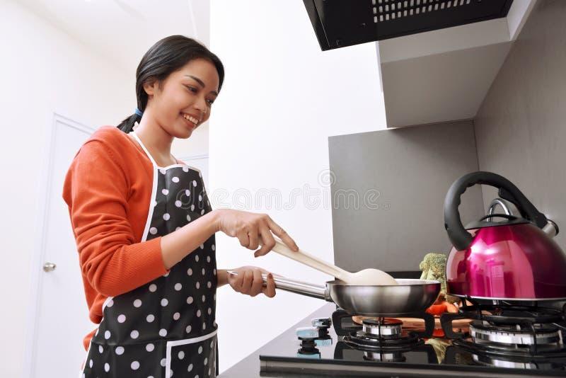 使用煎锅和烹调的微笑的亚裔妇女 图库摄影