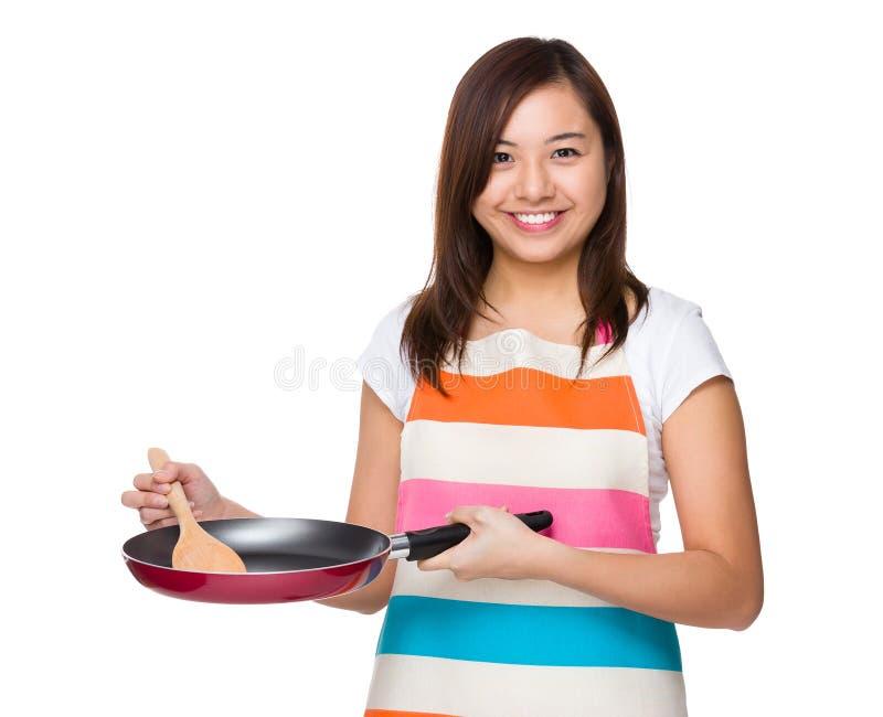 使用煎锅的年轻主妇 免版税库存照片