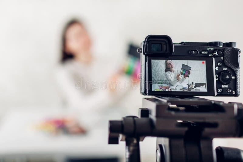 使用照相机和三脚架,年轻女人专业秀丽vlogger或博客作者录音组成讲解 免版税图库摄影