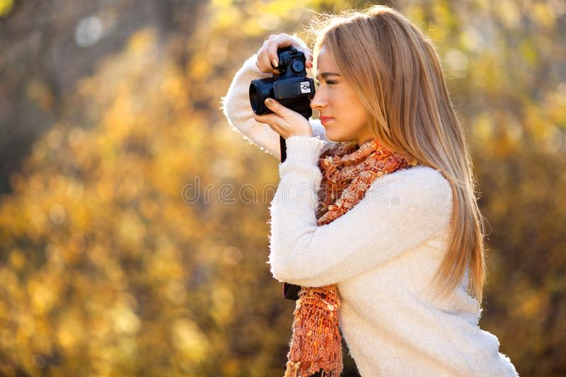 使用照相机的少妇在公园拍照片户外 库存照片