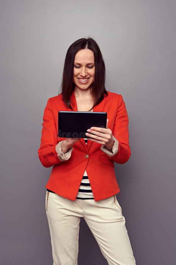 使用片剂个人计算机和微笑的女孩 免版税库存图片