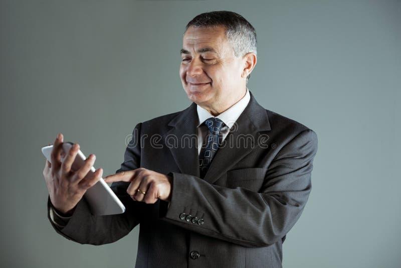 使用片剂个人计算机的一名愉快的老人的画象 库存照片
