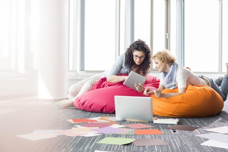 使用片剂个人计算机的创造性的女实业家,当放松在装豆子小布袋椅子在办公室时 免版税库存照片