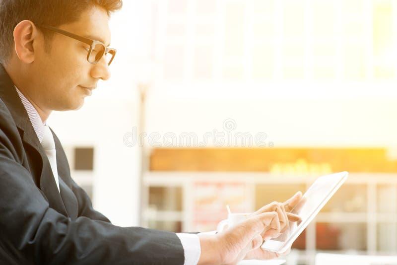 使用片剂个人计算机的印地安商人在咖啡馆 库存照片