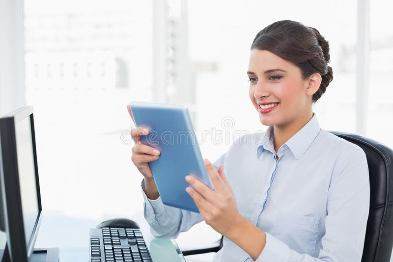 使用片剂个人计算机的发笑优等的棕色毛发的女实业家 免版税库存照片
