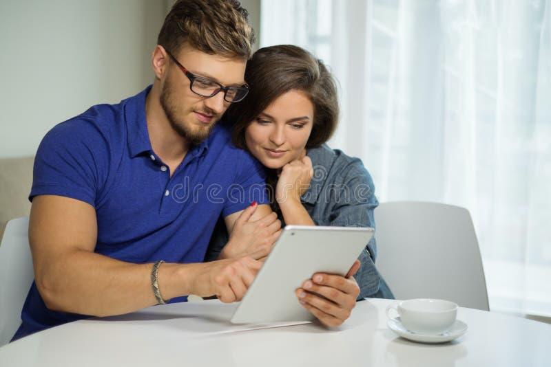 使用片剂个人计算机的夫妇在家 库存照片