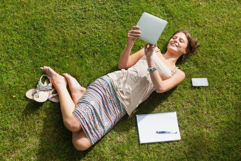 使用片剂个人计算机的女学生在公园 免版税库存图片
