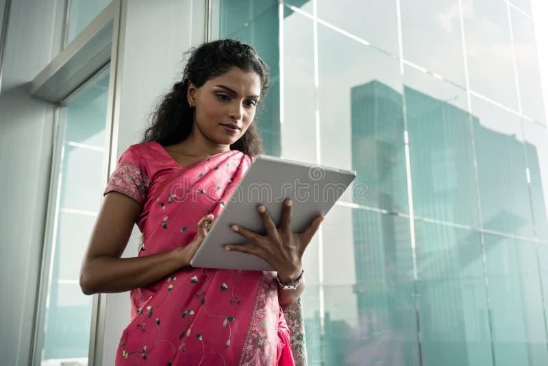 使用片剂个人计算机的年轻印地安妇女画象户外 免版税库存图片