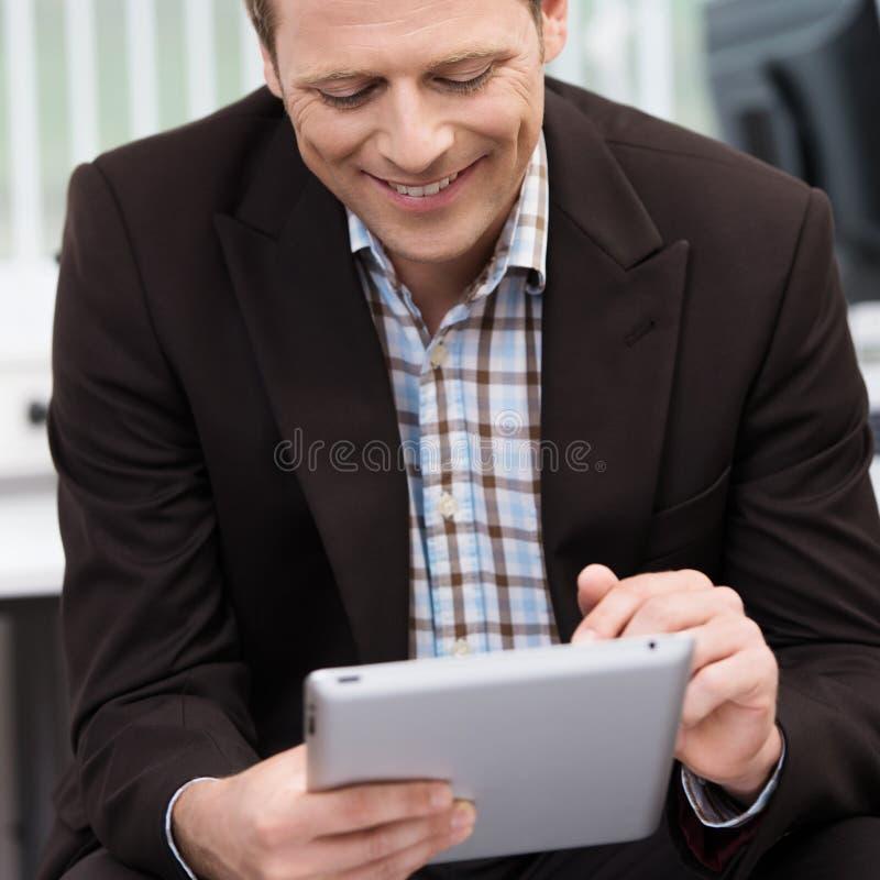 使用片剂个人计算机的微笑的人 库存图片