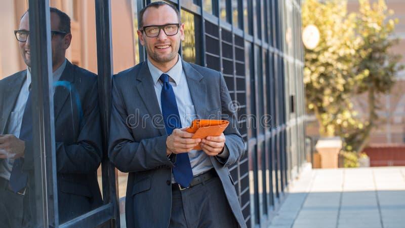使用片剂个人计算机的愉快的商人在城市str的橙色盖子 图库摄影