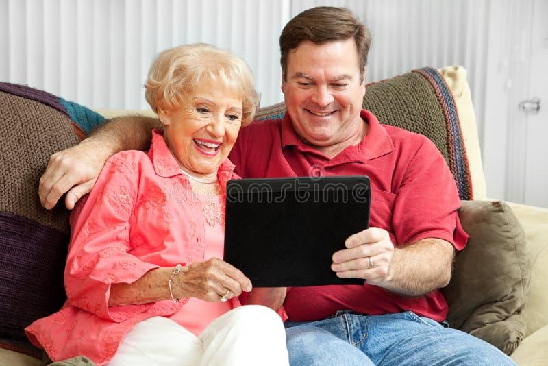 使用片剂个人计算机的母亲和儿子 库存图片