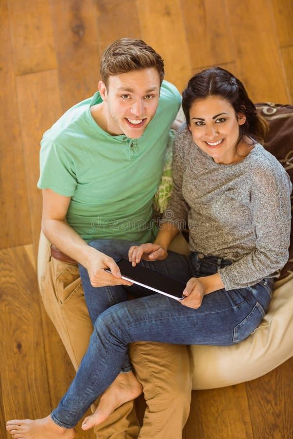 使用片剂个人计算机的逗人喜爱的夫妇在装豆子小布袋 免版税库存图片