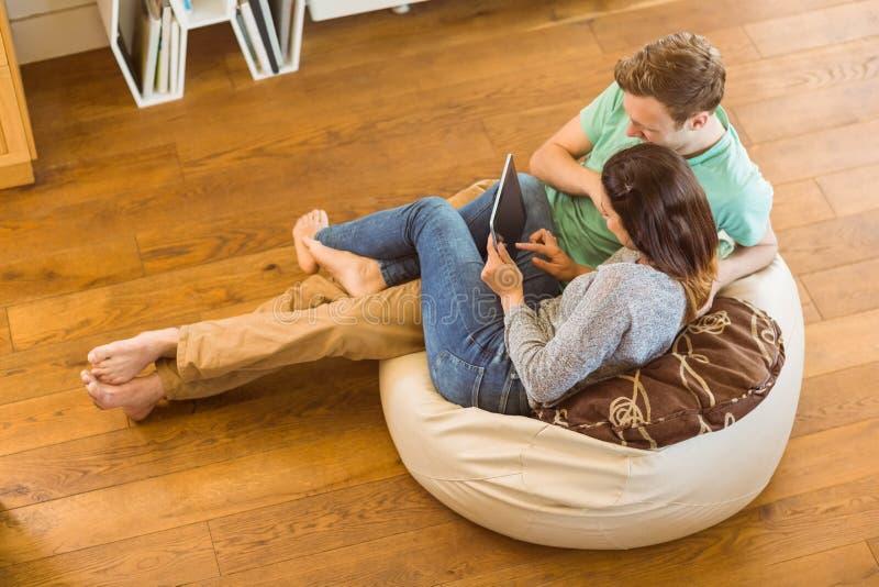 使用片剂个人计算机的逗人喜爱的夫妇在装豆子小布袋 图库摄影