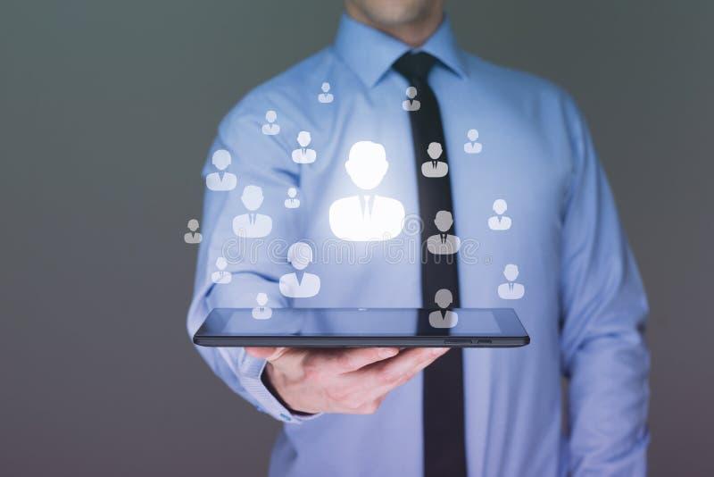 使用片剂个人计算机社交连接的商人 免版税库存图片