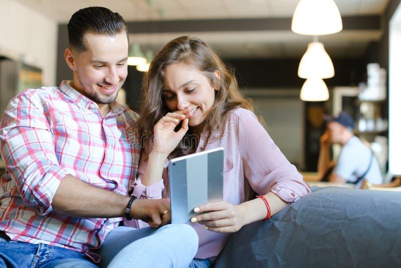 使用片剂和自由热点的年轻白种人男人和妇女在咖啡馆 库存图片