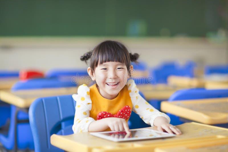 使用片剂或ipad的微笑的孩子 免版税图库摄影