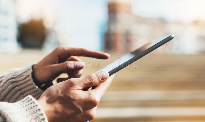 使用片剂技术互联网,博客作者人的行家女孩拿着在背景Sun City的计算机 免版税图库摄影