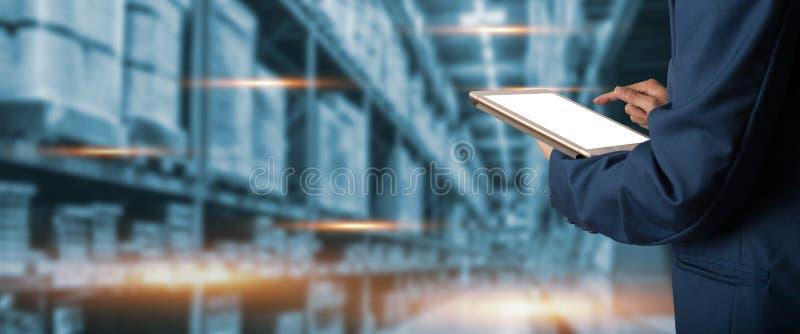 使用片剂检查和控制的商人经理为有现代商业仓库全球企业商务概念的工作者或 免版税库存照片