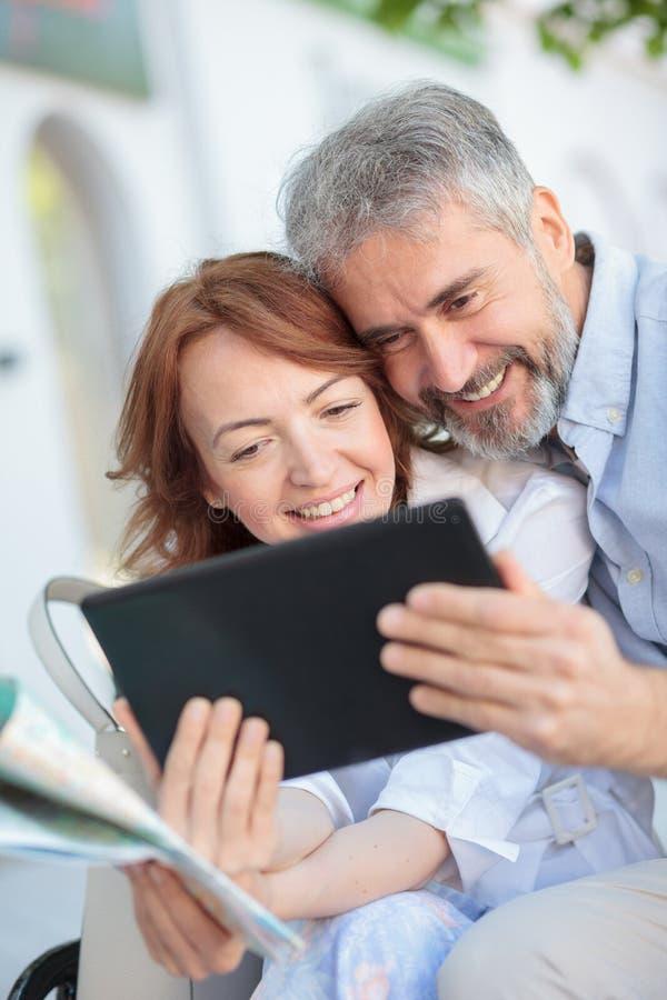 使用片剂的丈夫和妻子,当坐长凳时 库存图片