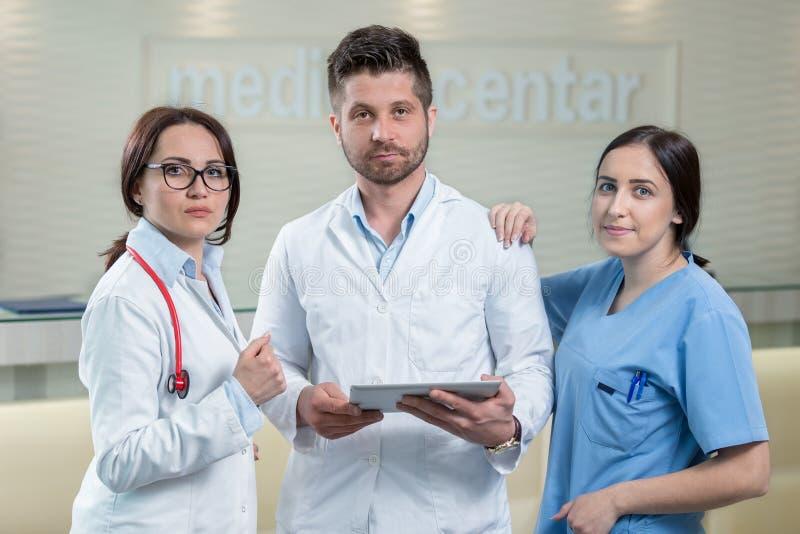 使用片剂的三位医生在一个明亮的办公室 免版税库存图片
