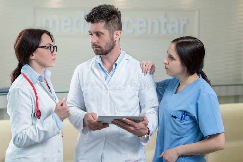 使用片剂的三位医生在一个明亮的办公室 免版税库存照片