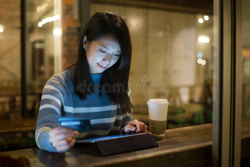 使用片剂的亚裔少妇为网上购物在咖啡馆 免版税库存照片