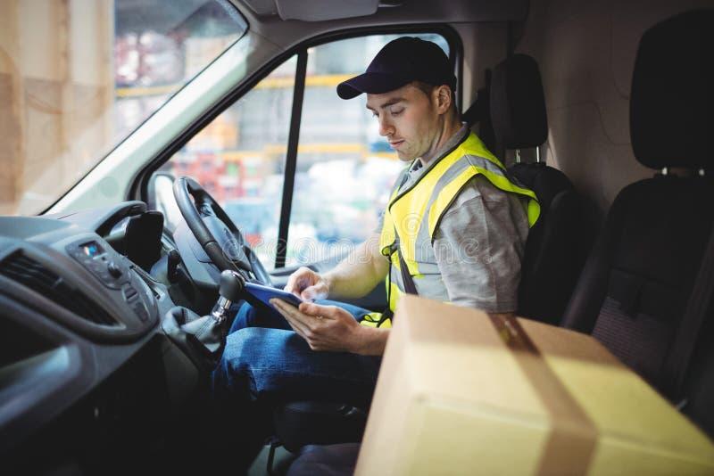使用片剂的交付司机在有小包的搬运车在位子 免版税库存图片