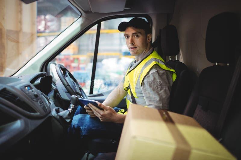 使用片剂的交付司机在有小包的搬运车在位子 免版税库存照片