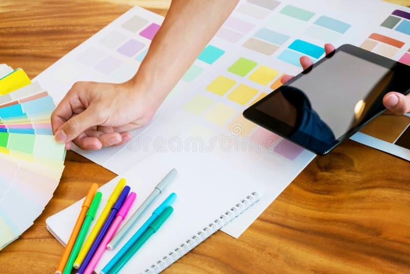 使用片剂的创造性的女商人和研究在书桌上的颜色图表在一个现代办公室 库存照片