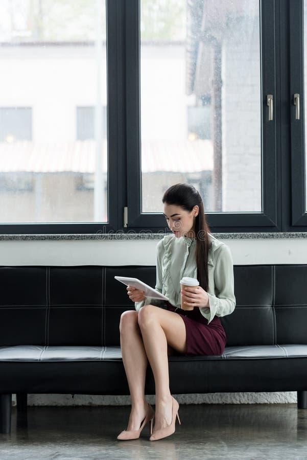 使用片剂的可爱的女实业家和拿着咖啡去在沙发 图库摄影