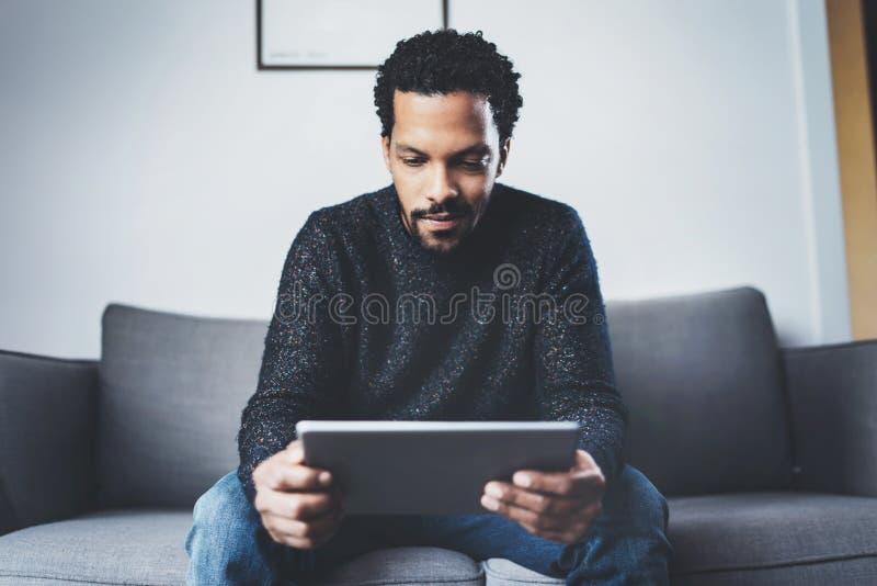 使用片剂的可爱的有胡子的非洲人,当坐沙发在他的现代办公室时 年轻商人的概念 免版税图库摄影