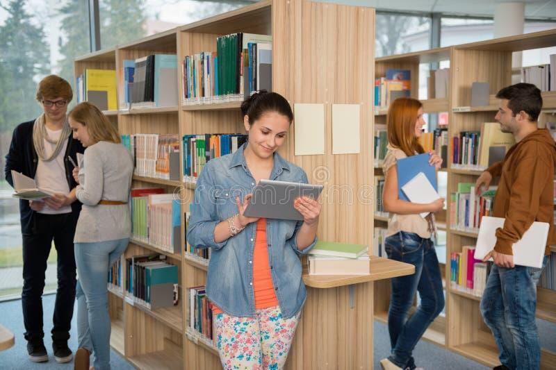 使用片剂的大学生在图书馆 免版税库存照片
