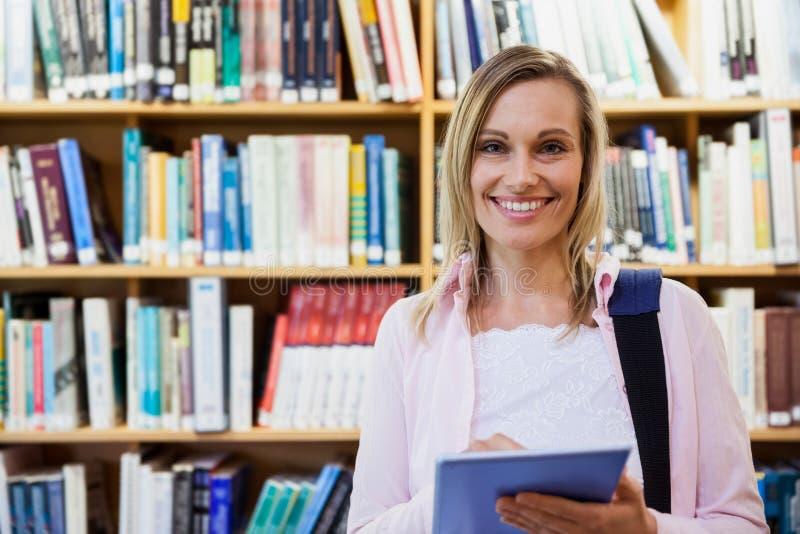 使用片剂的女学生在图书馆 库存图片