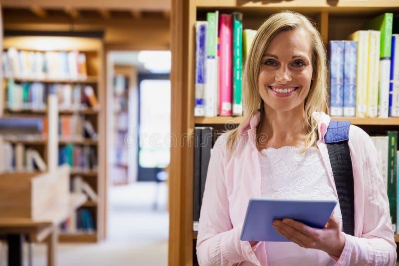 使用片剂的女学生在图书馆 库存照片
