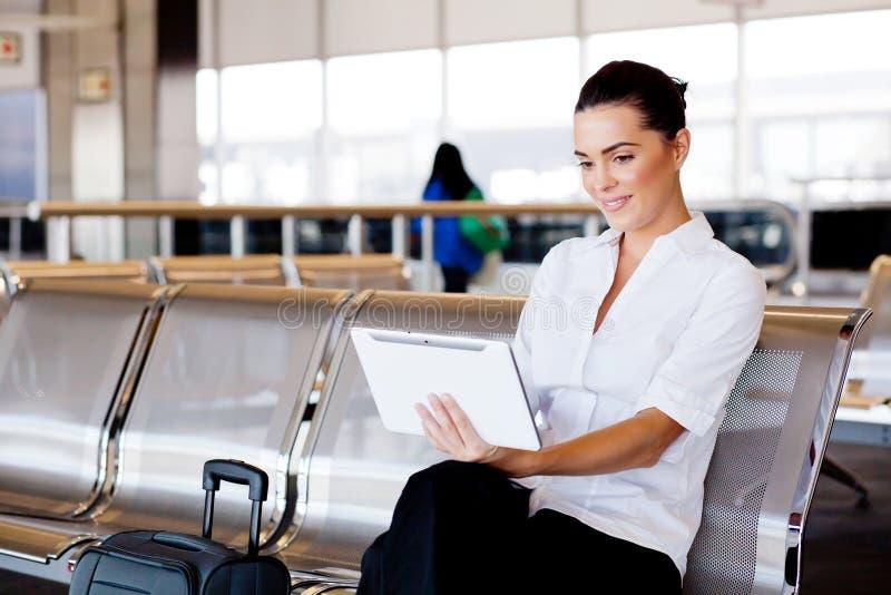 使用片剂的女实业家在机场 免版税库存图片