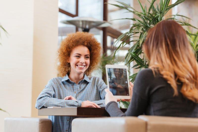 使用片剂的妇女为做照片她的女性朋友 免版税库存图片