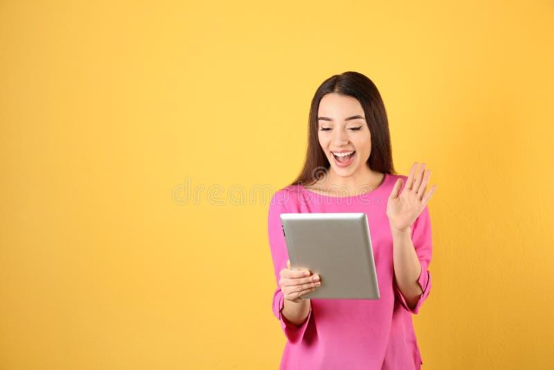 使用片剂的妇女为在颜色背景的视频聊天 免版税库存图片