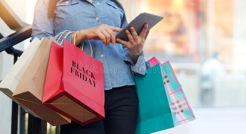 使用片剂的妇女和拿着黑星期五购物袋 免版税库存图片