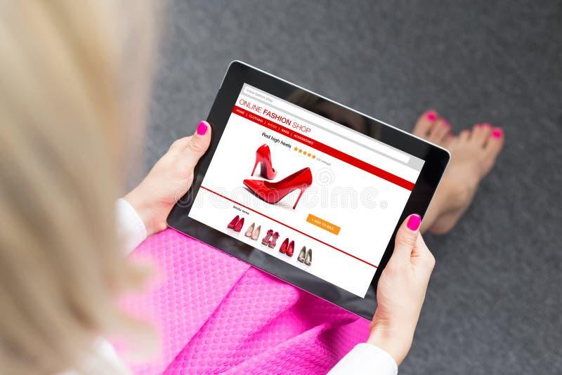 使用片剂的妇女在网上买鞋子 图库摄影