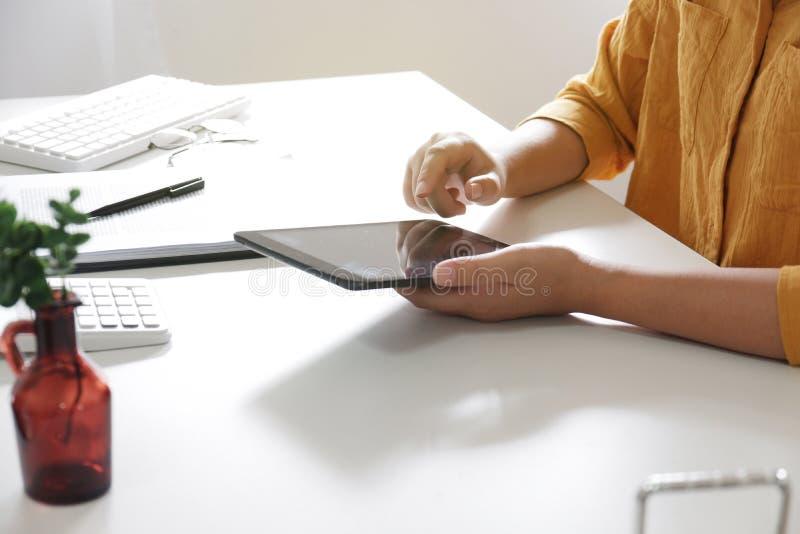 使用片剂的妇女,当工作在她的办公室时 库存图片