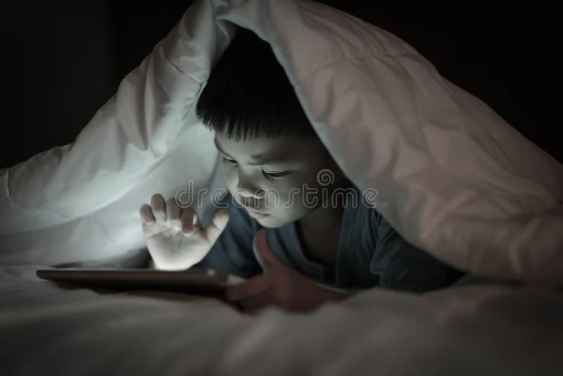 使用片剂的孩子,当说谎在毯子下时 库存图片