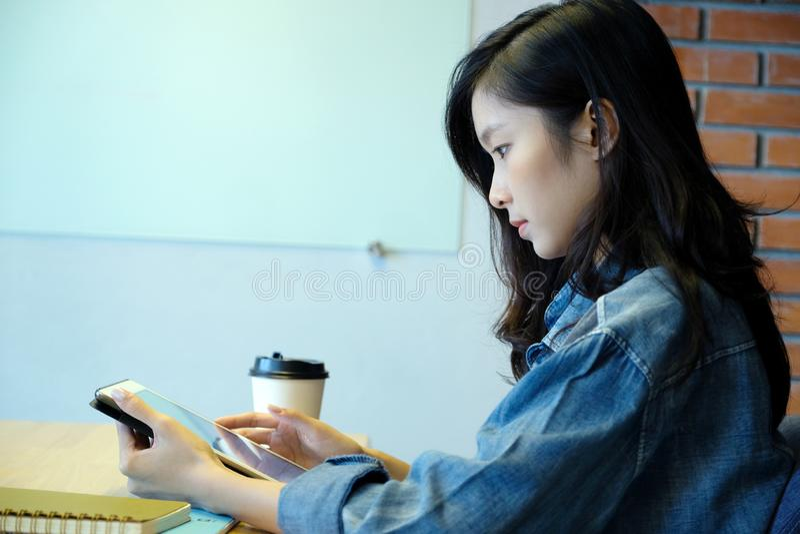 使用片剂的年轻亚裔妇女,当坐在屋子背景里时 免版税图库摄影