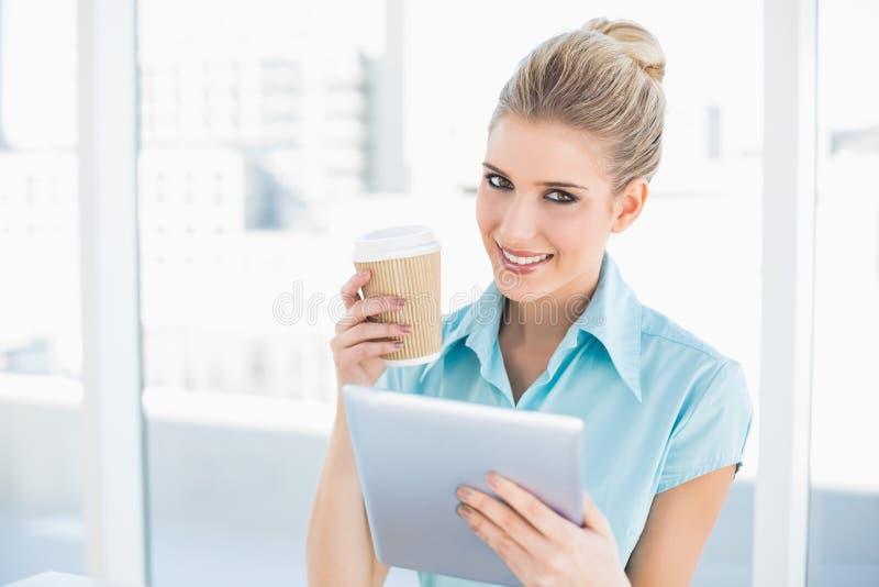 使用片剂的微笑的优等的妇女拿着咖啡 库存图片