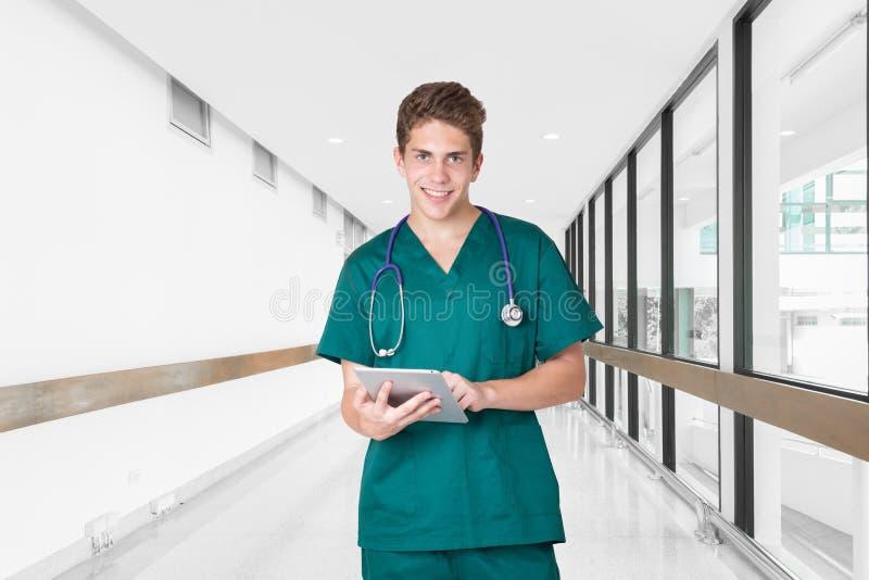 使用片剂的微笑的年轻医生在医院走廊 图库摄影