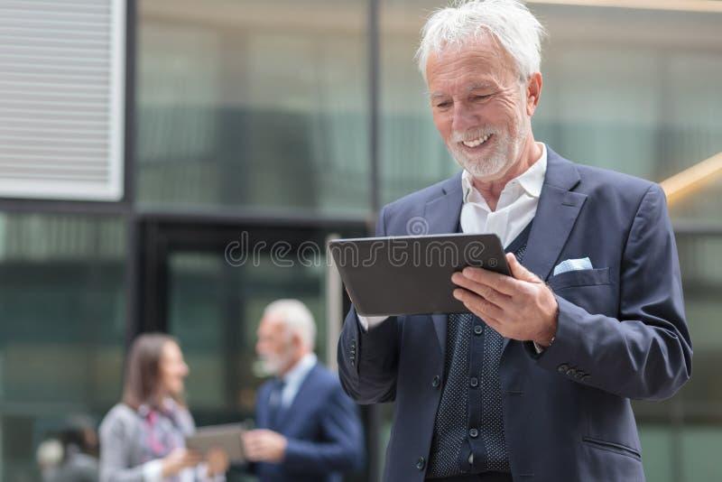 使用片剂的微笑的资深商人,站立在办公楼前面的一条边路 免版税库存照片
