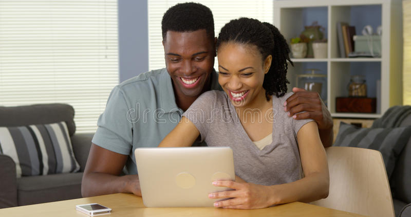 使用片剂的微笑的年轻黑夫妇一起 库存照片